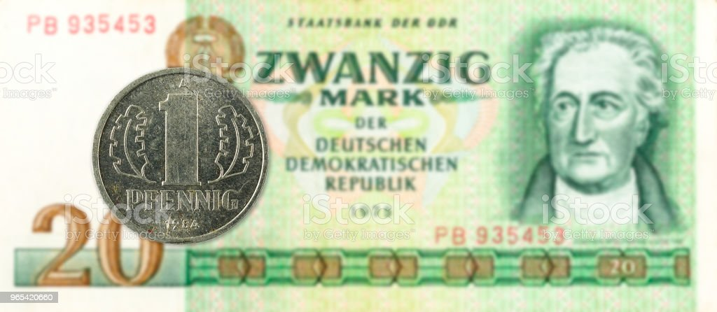 1 pfennig coin against historic 20 east german mark bank note royalty-free stock photo