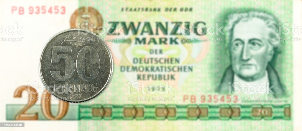 50 pfennig coin against historic 20 east german mark bank note royalty-free stock photo