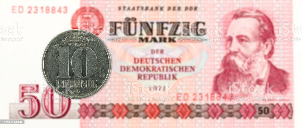 10 pfennig coin against historic 50 east german mark bank note royalty-free stock photo