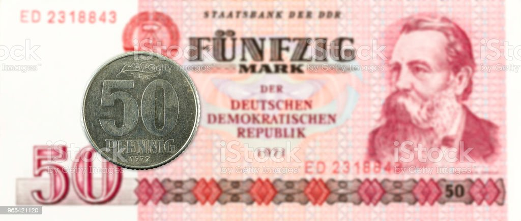 50 pfennig coin against historic 50 east german mark bank note zbiór zdjęć royalty-free