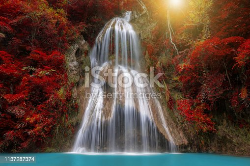 Waterfall in tropical deep forest with autumn color change Beautiful nature, Thailand.