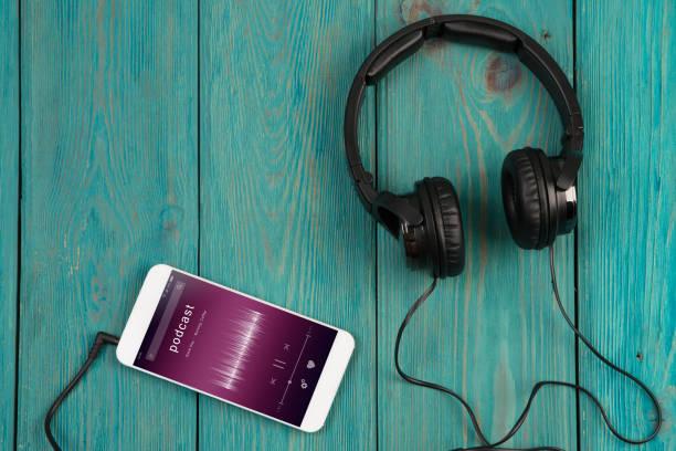 phablet en hoofdtelefoon op het houten bureau - podcast stockfoto's en -beelden