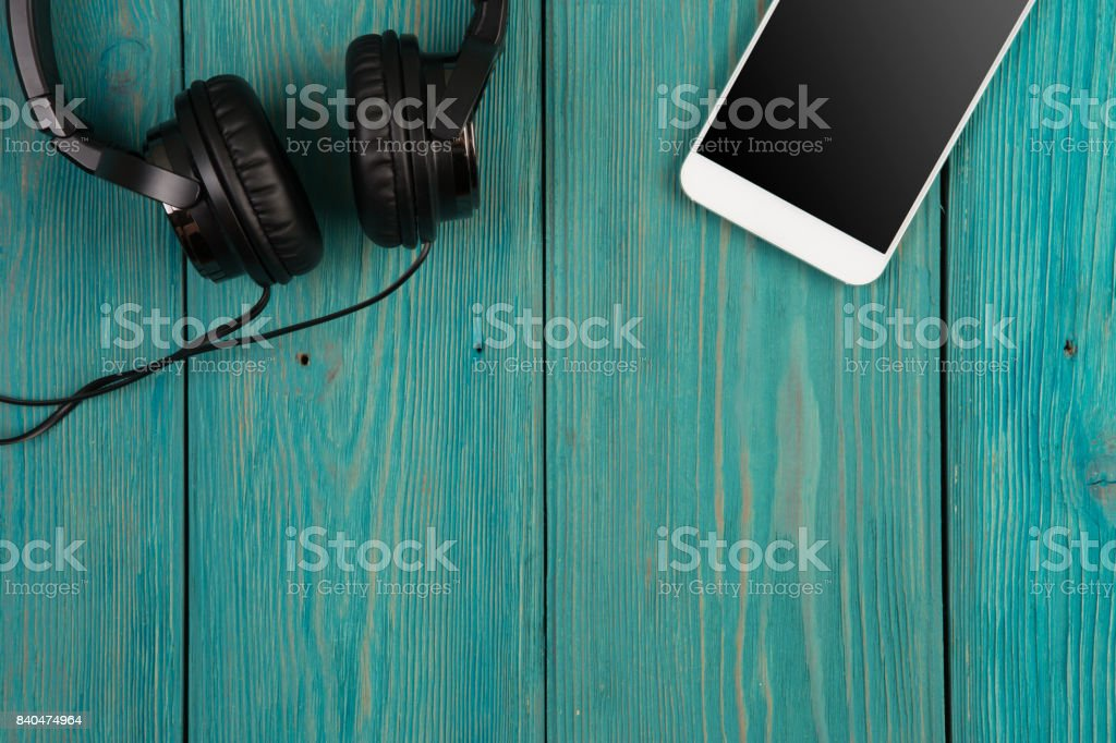 phablet and headphones on the wooden desk stock photo