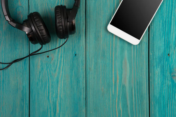 phablet and headphones on the wooden desk Music online concept - phablet and headphones on the wooden desk mp3 player stock pictures, royalty-free photos & images
