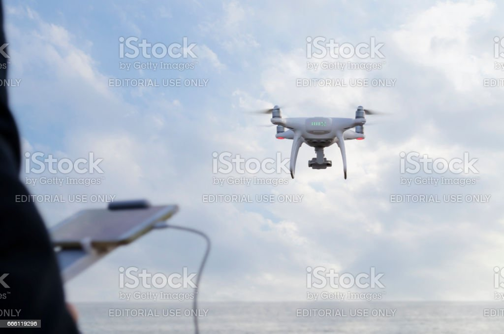 phantom drone at the cloudy sky and its remote control unit at man hands stock photo