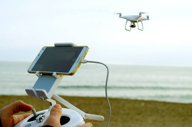 phantom drone at the sky and its remote control unit at man hands stock photo