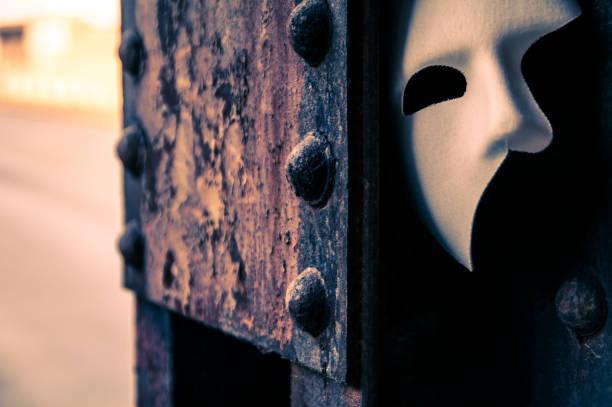 Phantom of the Opera mask on a dark gritty retro vintage steel bridge stock photo