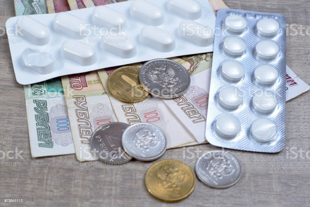 Pharmaceutical drugs and pills on Bank of Russia's banknotes, brown background stock photo