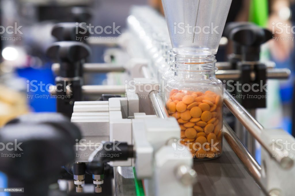 pharmaceutical industry, medicine pills are filling in the plastic bottle on production line machine conveyor at the medical factory. selective focus. stock photo