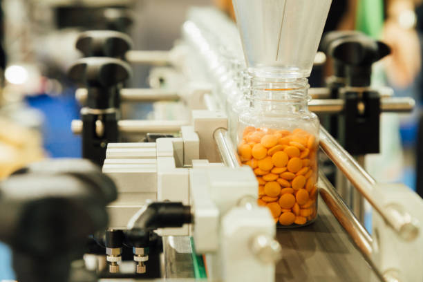pharmaceutical industry, medicine pills are filling in the plastic bottle on production line machine conveyor at the medical factory. selective focus. - pharmaceutical factory stock pictures, royalty-free photos & images