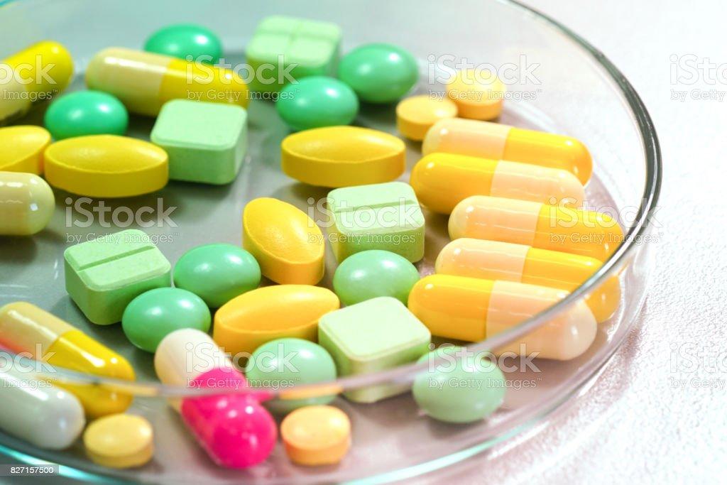 Pharmaceutical medicine pills in petri dish on table stock photo