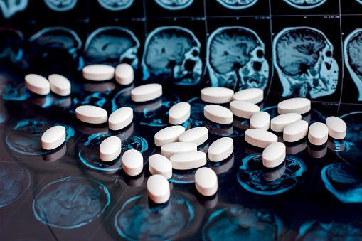 istock Pharmaceutical medicine pills on magnetic brain resonance scan mri background. Pharmacy theme, health care, drug prescription for tumor, alzheimer, mental illness treatment medication 1141943719