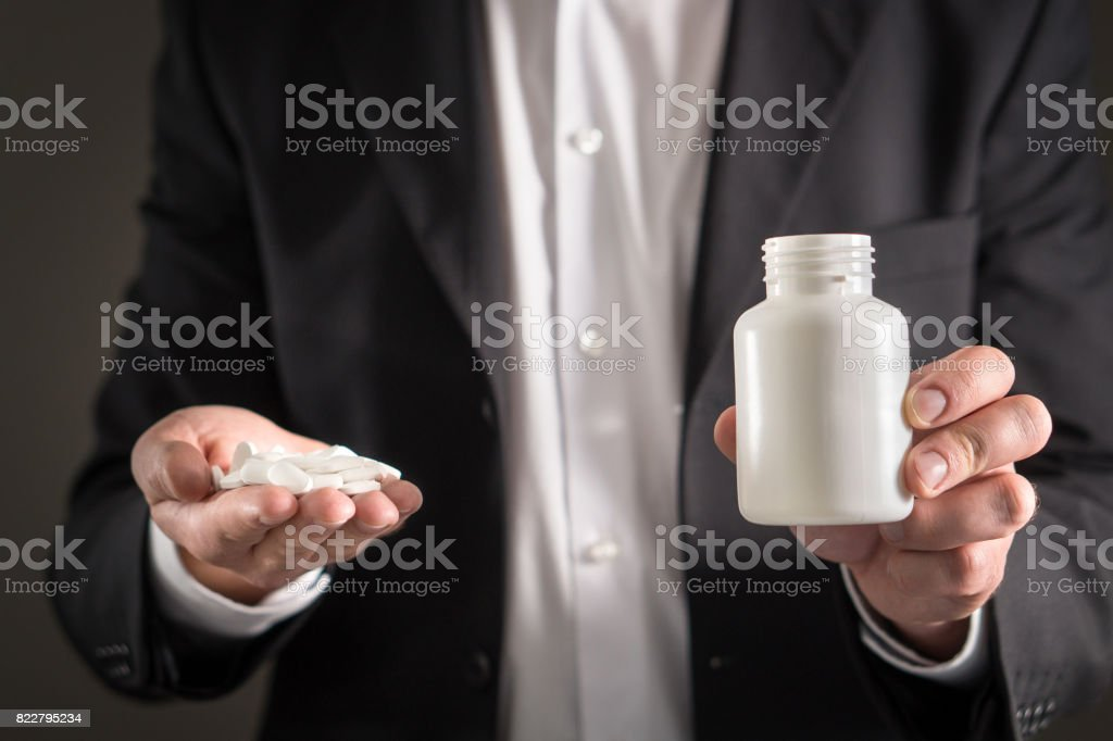 Pharmaceutical representative, consultant or head director or manager of medicine company with white tablets. Man in a suit holding pills and medicine bottle in hand. Medical business concept. stock photo