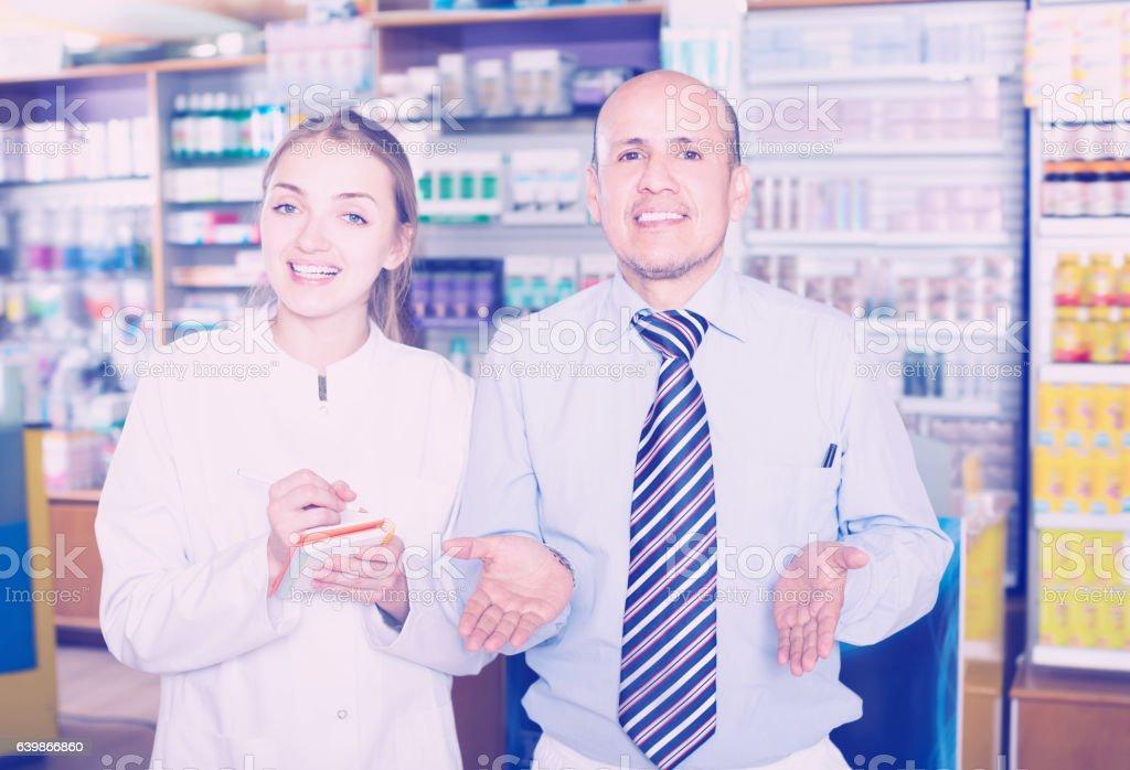 Pharmaceutist helping customer in drugstore stock photo