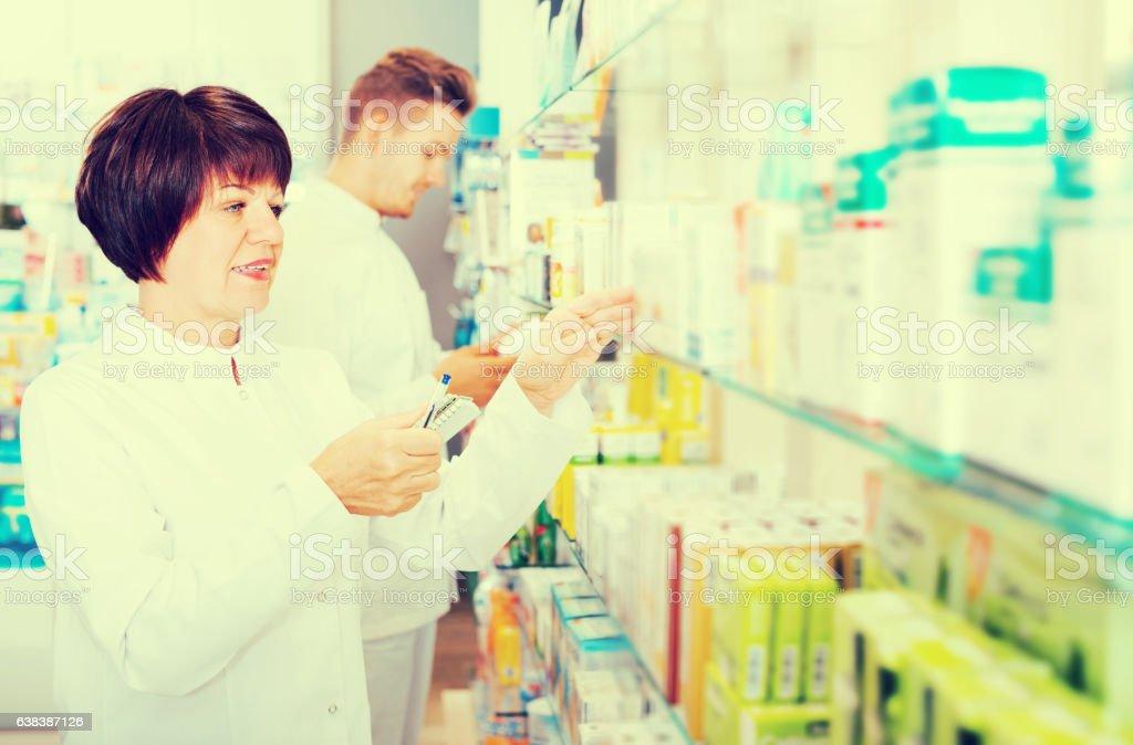 Pharmaceutist working in chemist shop stock photo