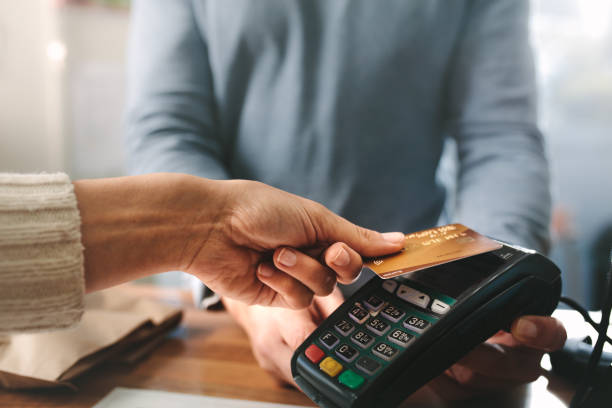 Pharmacist accepting credit card by contactless payment Pharmacist accepting credit card by contactless payment.  Woman purchasing products in the pharmacy. Pharmacist hands charging with credit card reader. credit card purchase stock pictures, royalty-free photos & images