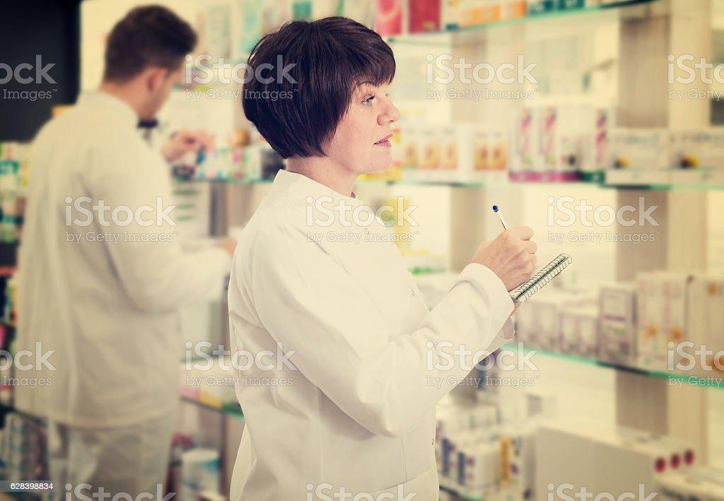 Pharmacist and pharmacy technician posing in drugstore stock photo