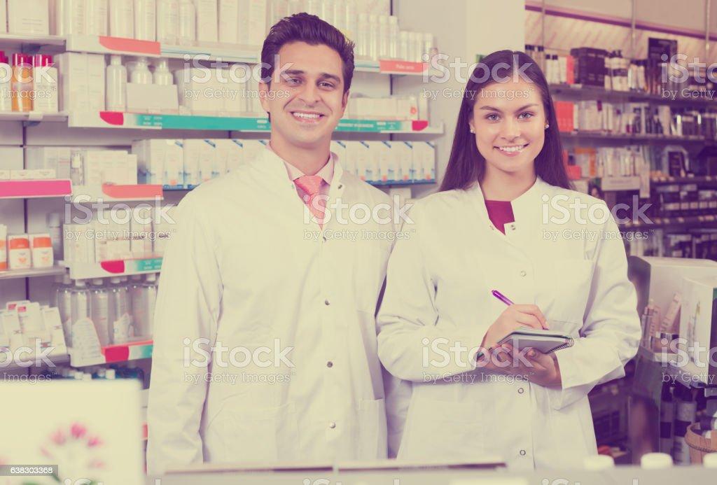 Pharmacist and pharmacy technician posing stock photo