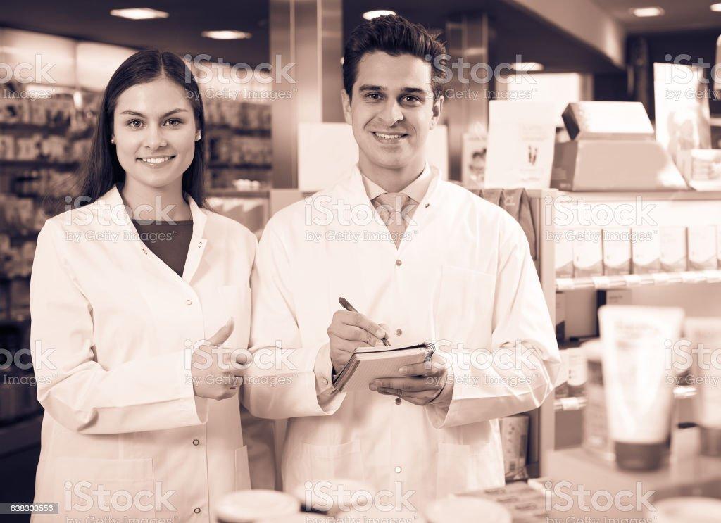 Pharmacist and pharmacy technician working stock photo