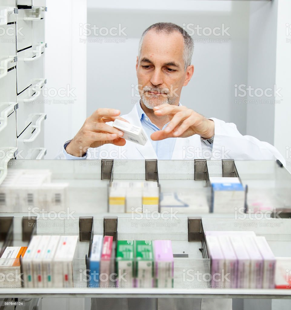 Pharmacist at his pharmacy ordering drugs stock photo