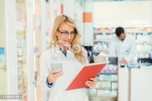 young pharmacist checking medication details, pharmacist using tablet