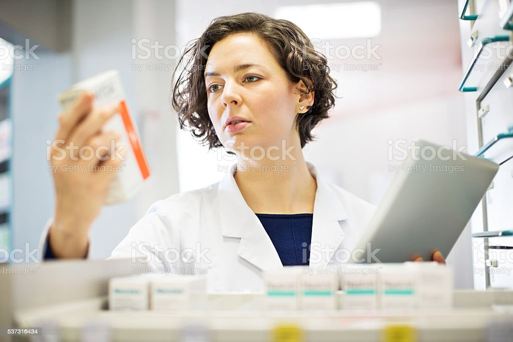 Pharmacist checking medication inventory at pharmacy store stock photo