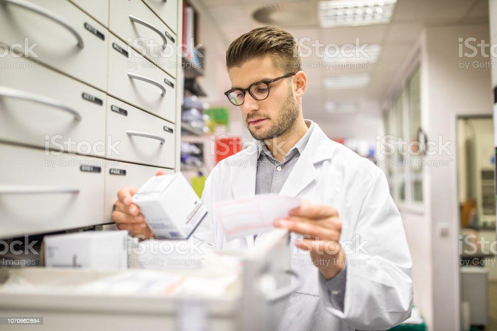 Apotheker überprüfen Arzneimittel auf rack – Foto