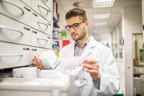 apotheker überprüfen arzneimittel auf rack - papierrollenhalter stock-fotos und bilder
