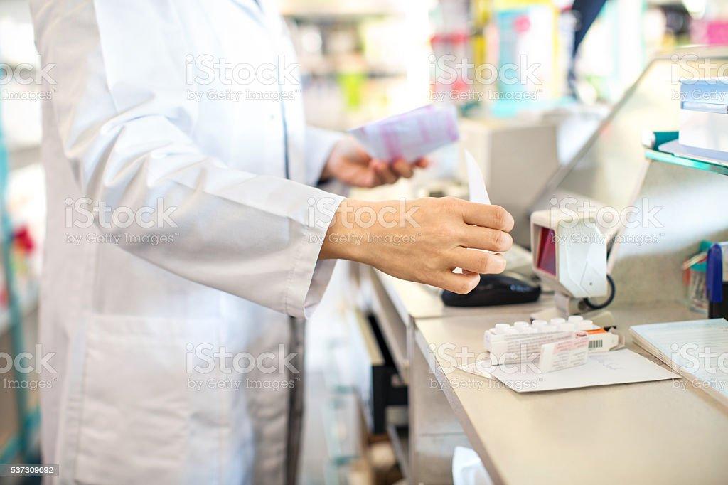 Pharmacist checking out customer's medication prescription stock photo
