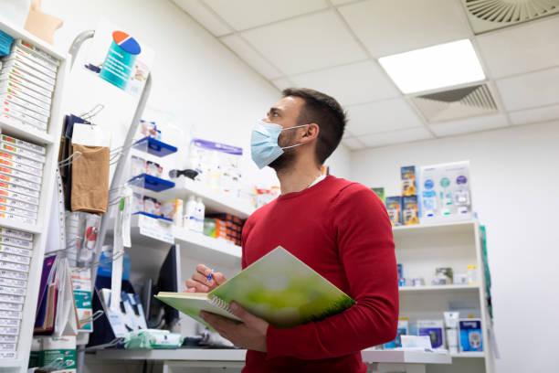 Apotheker überprüft Vorräte und trägt schützende OP-Maske im Shop – Foto