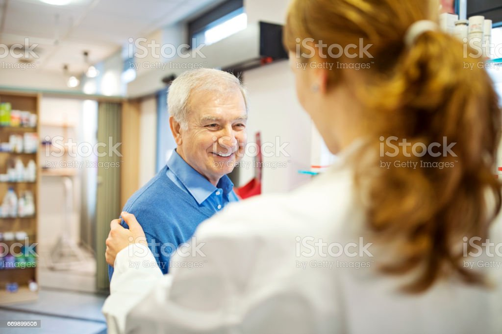 Pharmacist consoling senior man in store stock photo