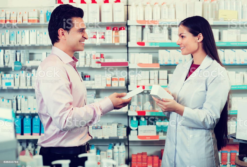 Pharmacist counseling customer about drugs stock photo