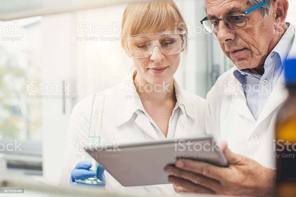Pharmacist Discussing and Using Digital Tablet stock photo