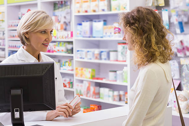 Pharmacist explaining the drug to patient stock photo