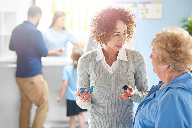 pharmacist explains to asthmatic customer stock photo