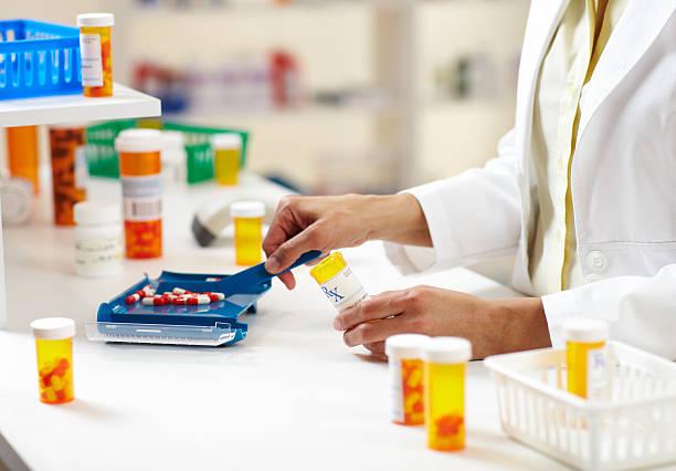 Pharmacist Filling Prescription of Pills stock photo