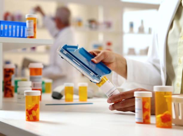 pharmacist filling prescription - riempire foto e immagini stock