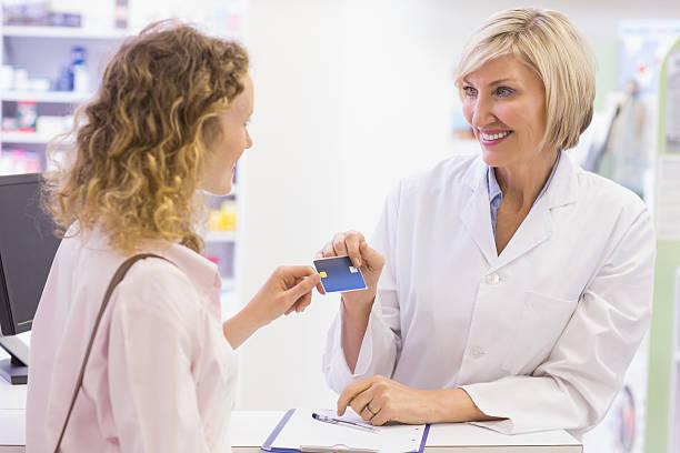 farmacêutico dando cartão de crédito de cliente - costumer - fotografias e filmes do acervo