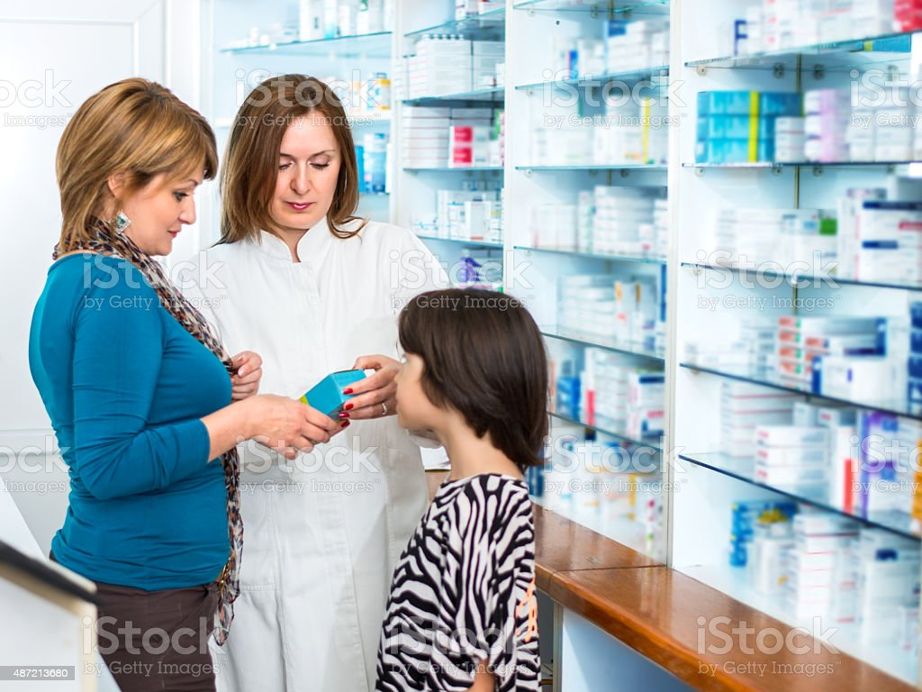 1e289f59390 Pharmacist Giving Medication To A Mother And Daughter stock photo ...