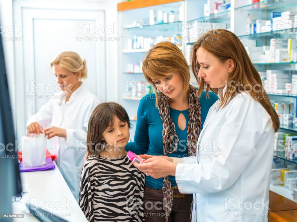 ae4cc24940e Pharmacist giving medication to a mother and daughter royalty-free stock  photo