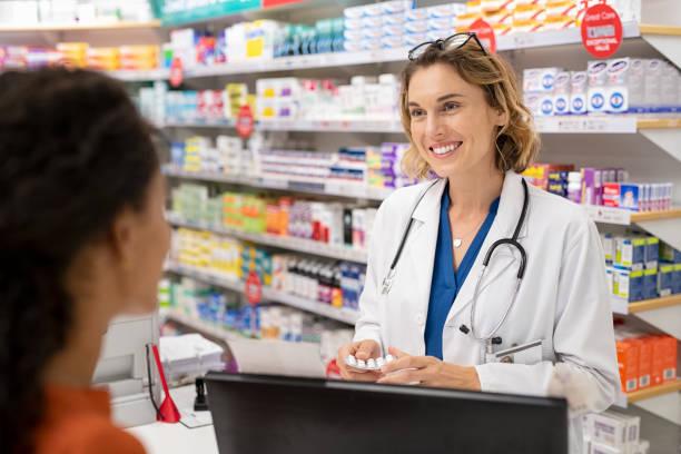 Pharmacist giving medicine to customer stock photo