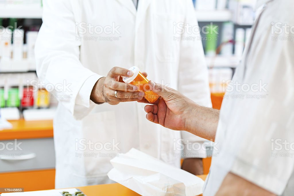 Pharmacist giving pill bottle to customer at hte pharmacy royalty-free stock photo