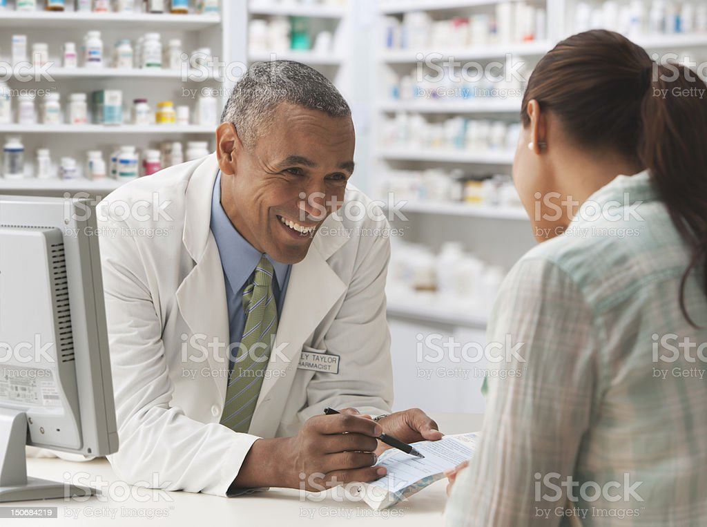 Pharmacist going over prescription with customer​​​ foto