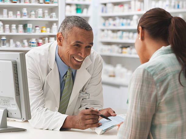 Pharmacist going over prescription with customer stock photo