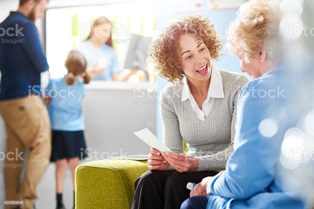 A female pharmacist sits with a senior female patient in the...
