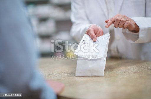 A pharmacist in a white lab coat holds out a processed and packaged prescription as he explains how to properly and safely take the medication.  The patient is dressed casually and standing on the other side of the counter.  Only the patient and pharmacists hands can be seen.