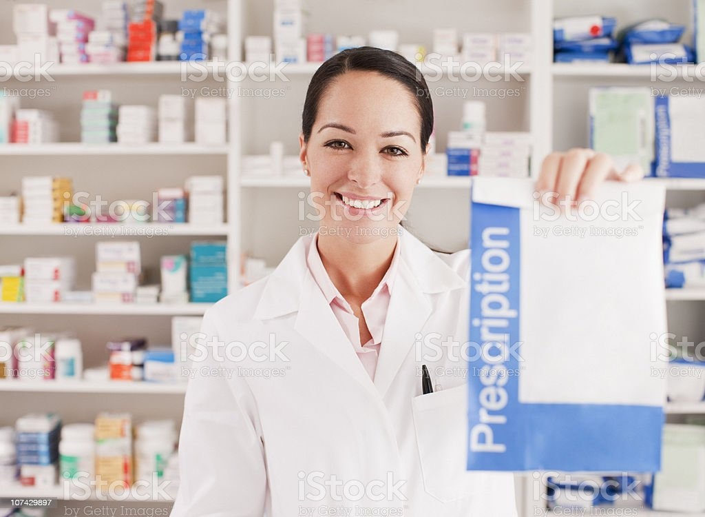 Pharmacist holding prescription in drug store stock photo