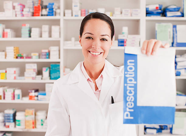 Pharmacist holding prescription in drug store stock photo