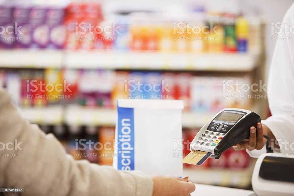 Pharmacist holding security device for customer in drug store stock photo