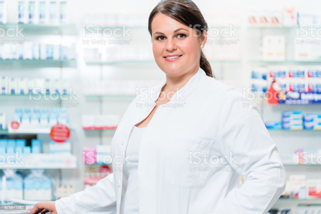 Pharmacist in chemist shop looking at camera royalty-free stock photo